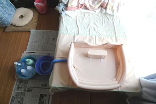ベットに洗髪機を設置した様子