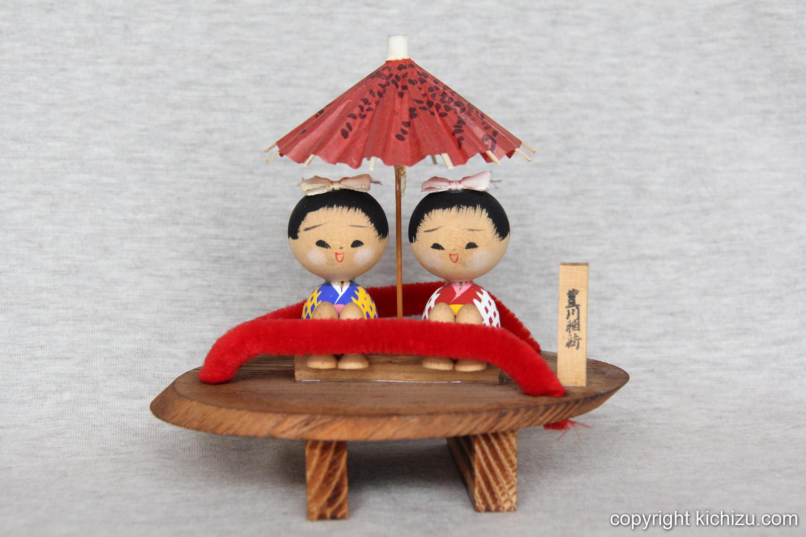 傘を差した夫婦の置物