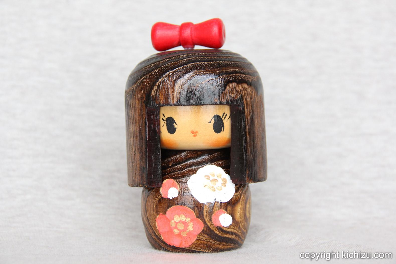 リボンを付けた女の子の木製人形
