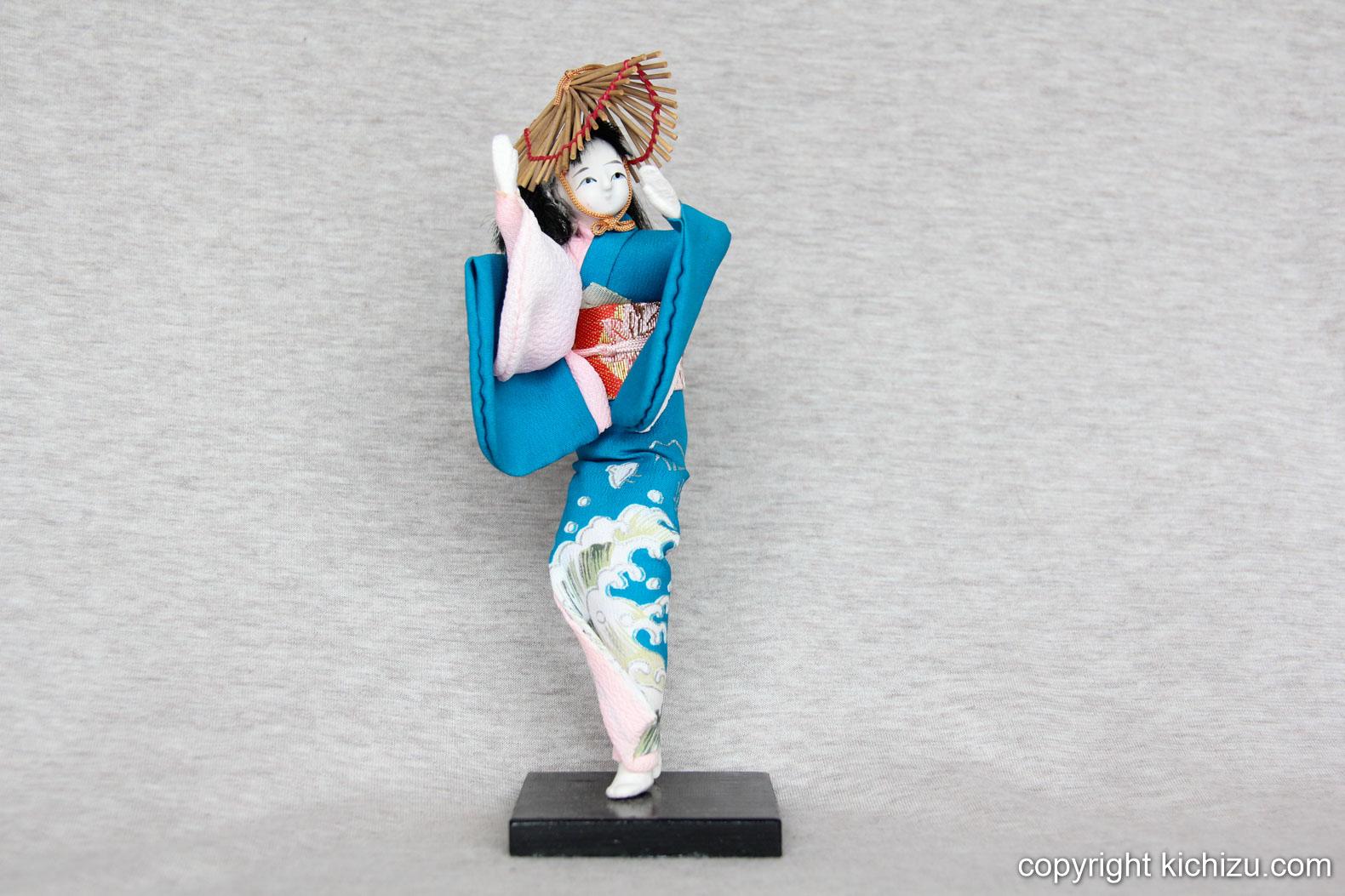 波しぶきがデザインされた着物を着て踊っている女性のお人形。