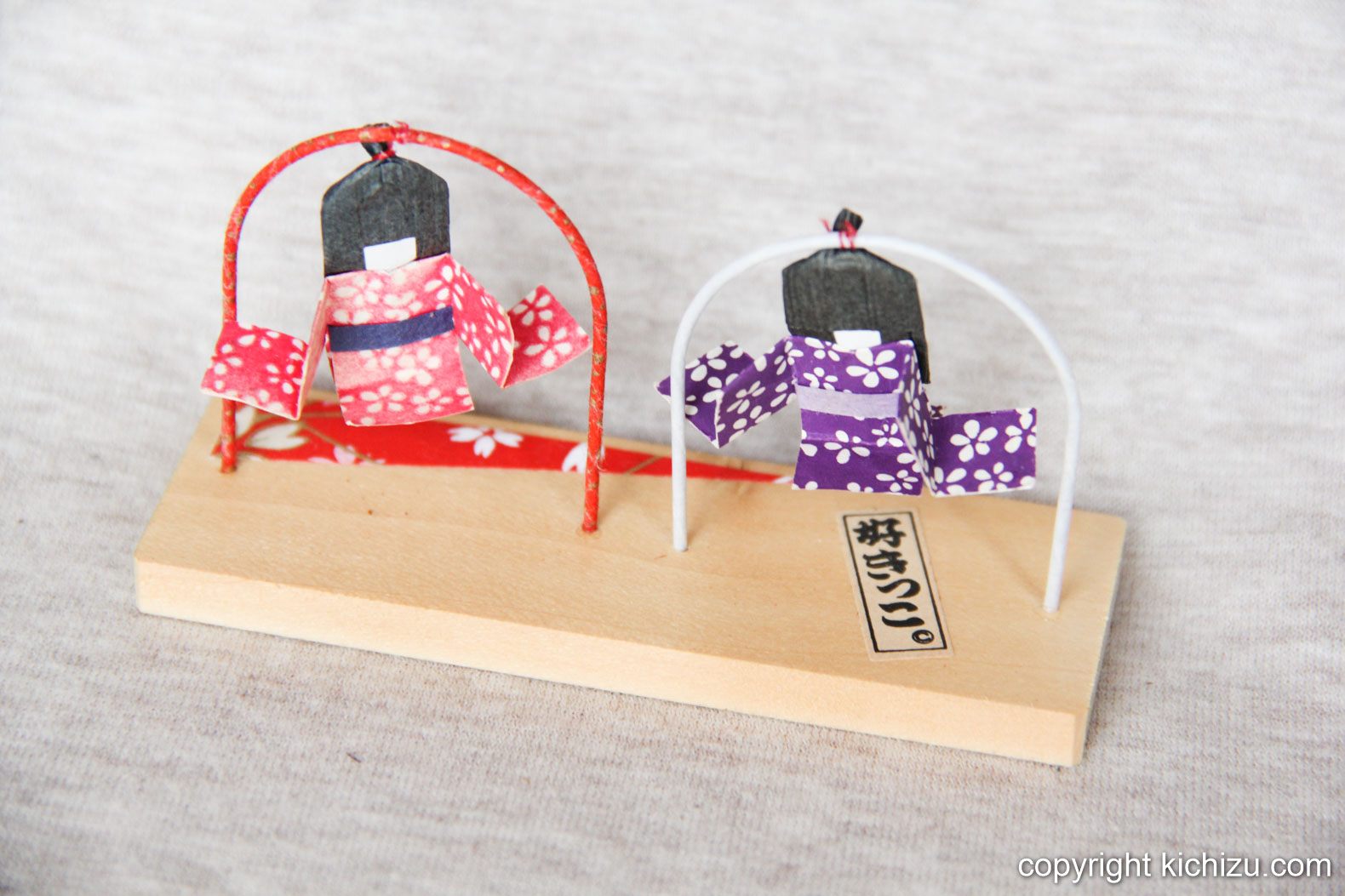 折り紙で出来た夫婦の人形。輪っかに紐でぶら下がっており、風で揺れ動く。