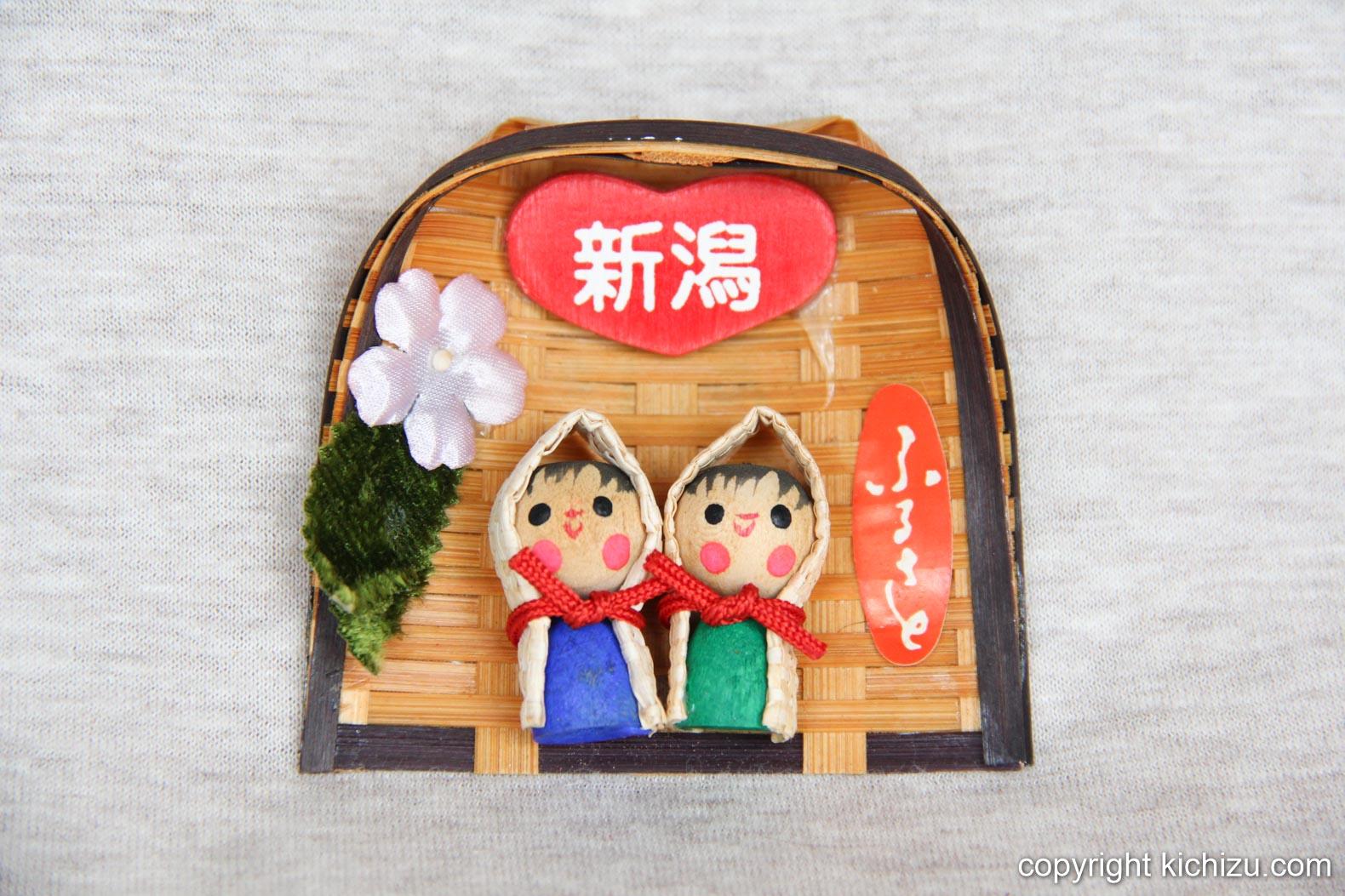 頭巾をかぶった青と緑の夫婦人形。上にはハートの形をしたアクセントに「新潟」の文字。