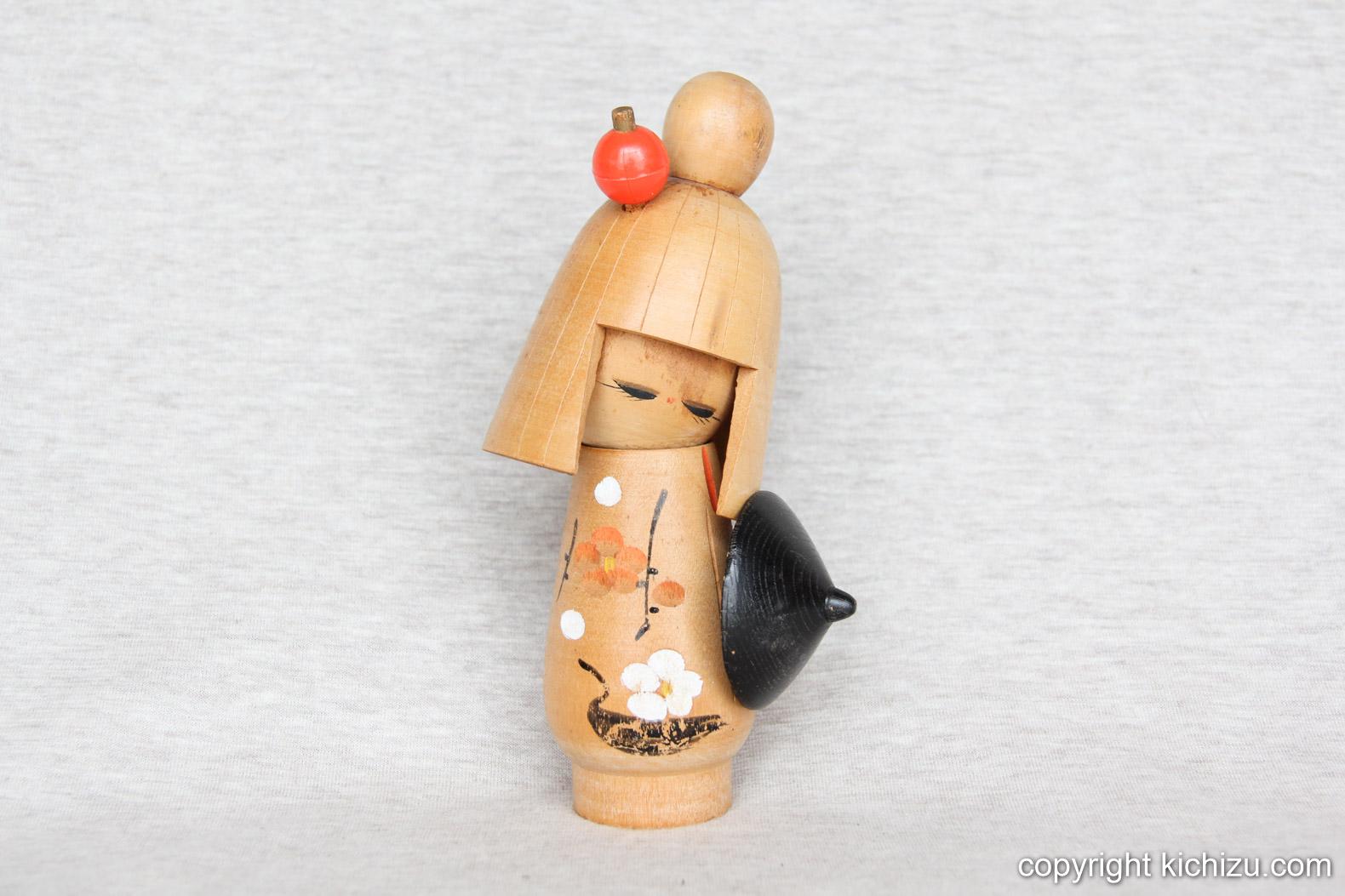 赤い簪(かんざし)を付け、黒い傘を持つ女性。洋服には桜と鶴が描かれている